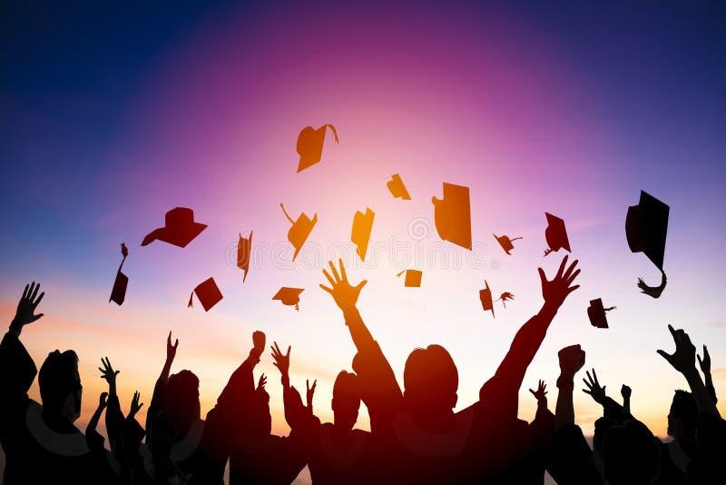 学生在天空中的投掷毕业盖帽 库存图片