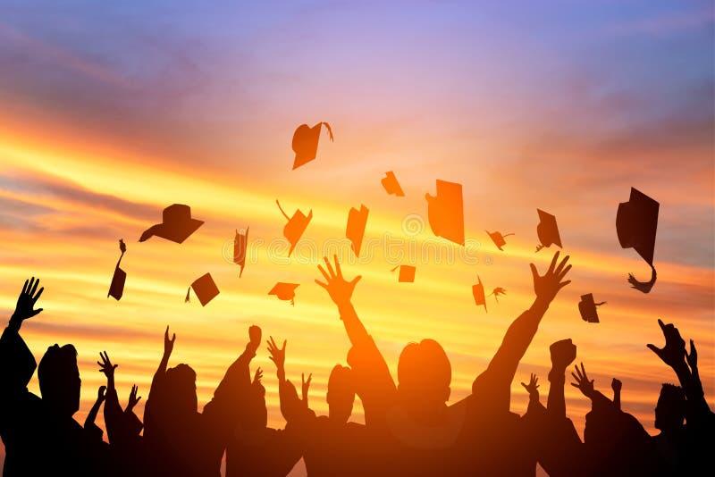 学生在天空中的投掷毕业盖帽 库存照片