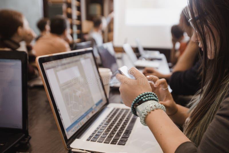学生在教室与膝上型计算机一起使用 图库摄影