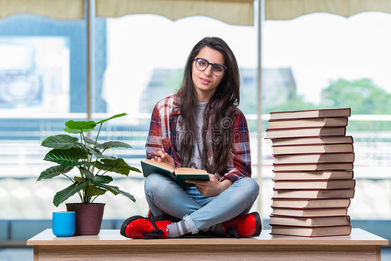 学生坐有书的书桌 免版税图库摄影