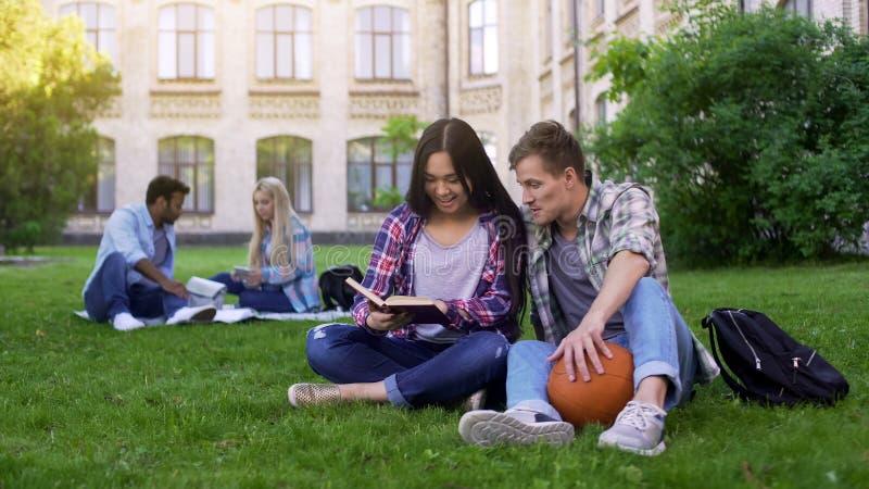 学生夫妇坐在校园里的草坪,学习,为最后试验做准备 免版税库存照片