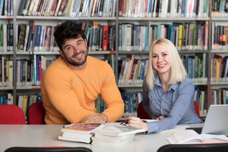 学生夫妇有膝上型计算机的在图书馆里 免版税库存照片