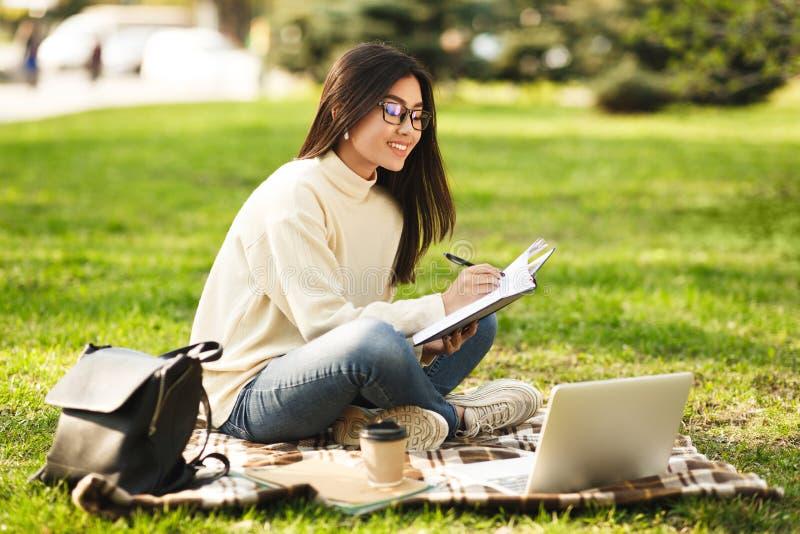 学生女孩为演讲做准备使用膝上型计算机 免版税库存图片