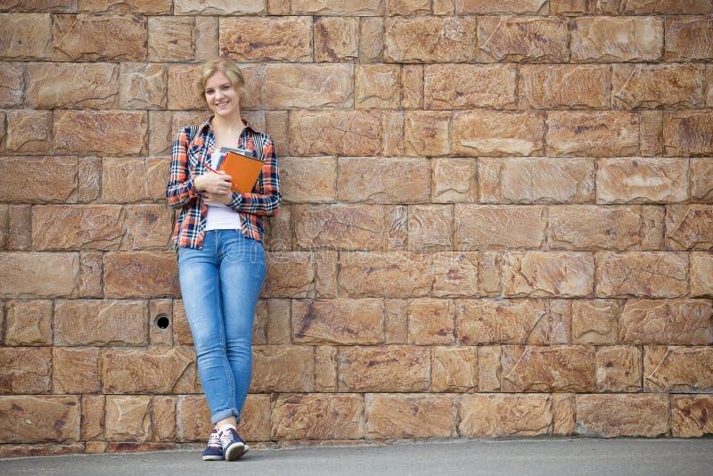 学生女孩全长画象对有课本的砖墙 图库摄影