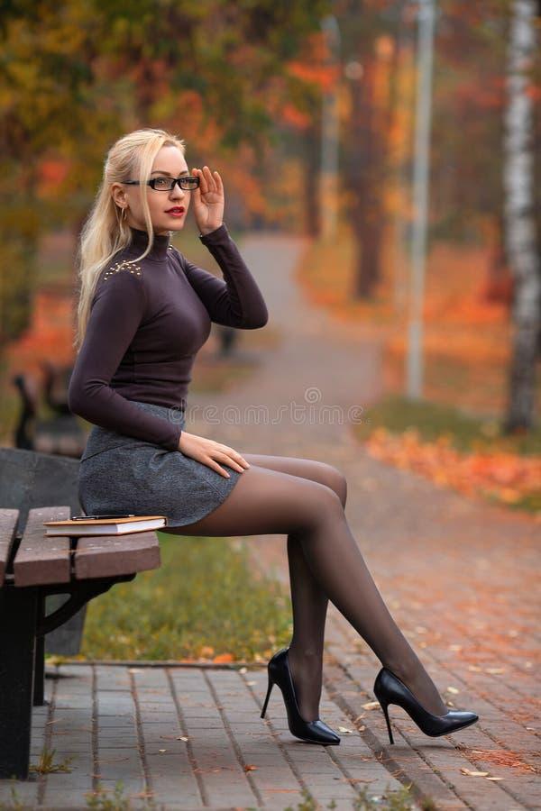 学生女孩坐长凳在秋天公园 库存图片