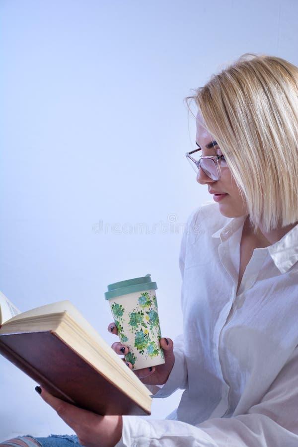 学生女孩看书和饮用的热的茶从减速火箭的杯子 免版税库存图片