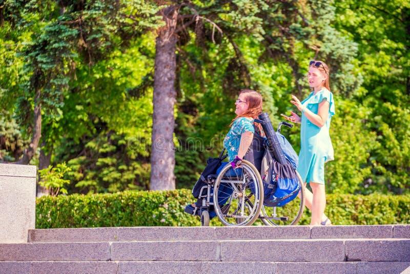 学生女孩走与她的朋友到在一个轮椅的残疾开会沿伏尔加河堤防在一个晴朗的夏天da 库存照片