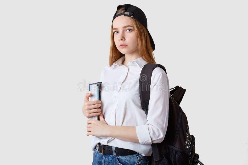 学生女孩身分水平的射击被隔绝在白色背景,在手上拿着纸文件夹,佩带的女衬衫,黑盖帽 免版税库存照片