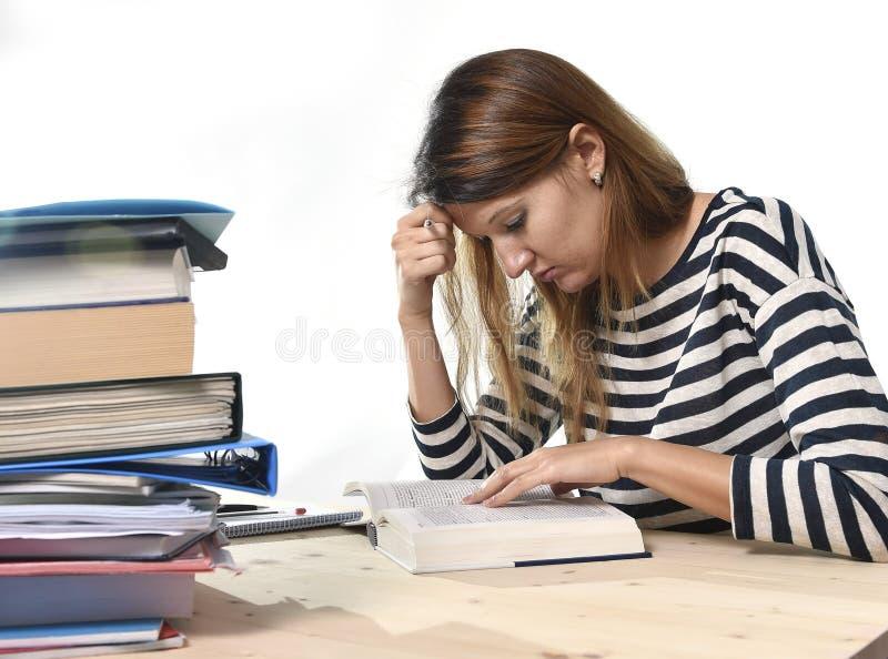 年轻学生女孩集中了学习检查的在大学图书馆教育概念 免版税图库摄影