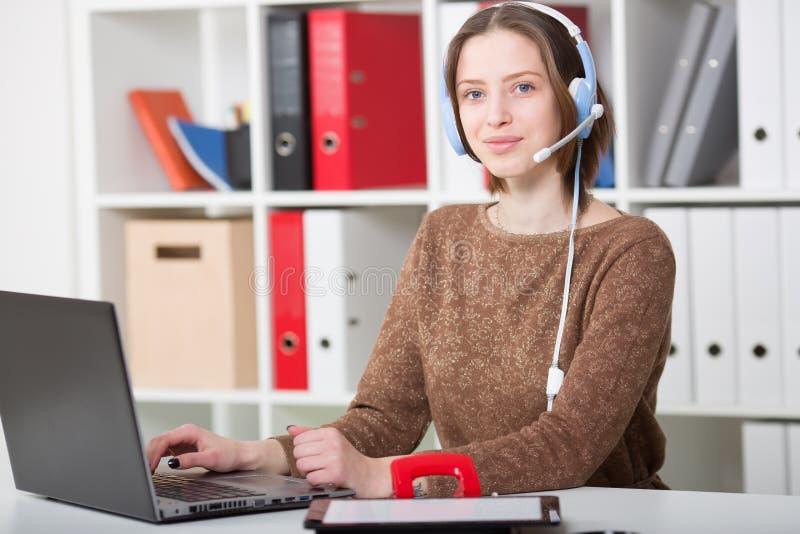 学生妇女为网上学习的大学使用有话筒的一个耳机 免版税库存照片