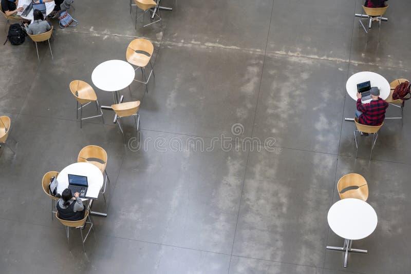 学生学习在坐在现代教育机构大厅的桌上的膝上型计算机的教材  库存照片