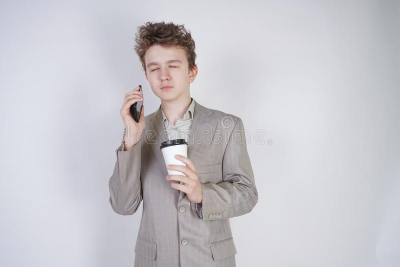 学生少年与闭合的眼睛的男孩身分用咖啡和智能手机 非常在白色st的疲乏的年轻男性佩带的西装 免版税图库摄影
