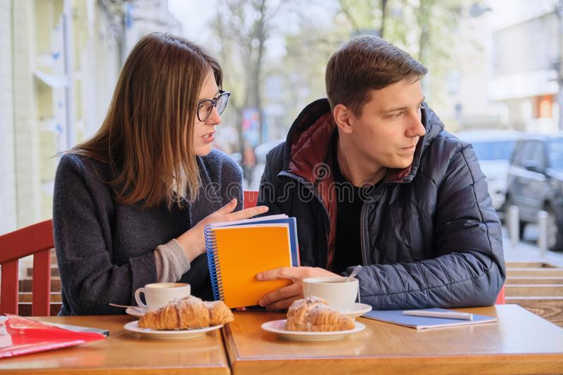 学生年轻夫妇在室外咖啡馆,饮料咖啡茶学习,吃新月形面包,背景是春天城市街道 库存图片