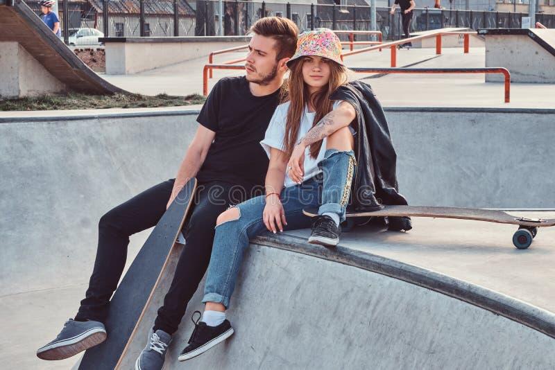 学生年轻有吸引力的夫妇坐在与他们的longboards的skatepark 库存照片