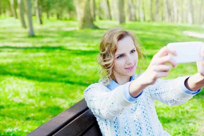 年轻学生微笑的女孩拍在室外智能手机的照相机的selfie照片 免版税库存图片