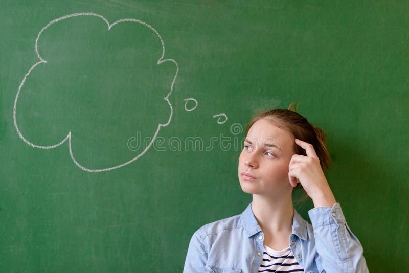 学生想法的黑板概念 看在黑板背景的沉思女孩想法泡影 免版税库存照片