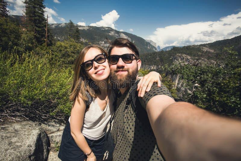 学生愉快的微笑的夫妇爱的采取selfie自画象,当远足在优胜美地国家公园,加利福尼亚时 免版税图库摄影