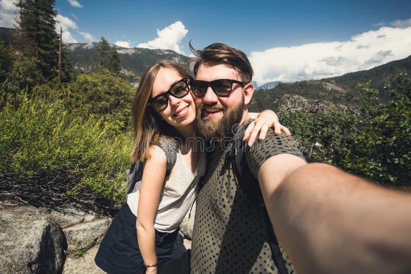 学生愉快的微笑的夫妇爱的采取selfie自画象,当远足在优胜美地国家公园,加利福尼亚时 免版税库存图片