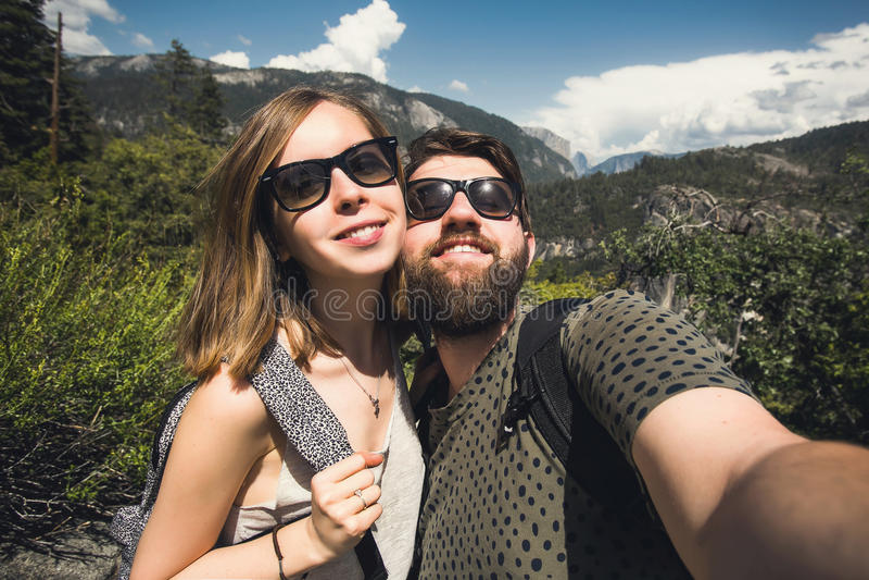 学生愉快的微笑的夫妇爱的采取selfie自画象,当远足在优胜美地国家公园,加利福尼亚时 图库摄影