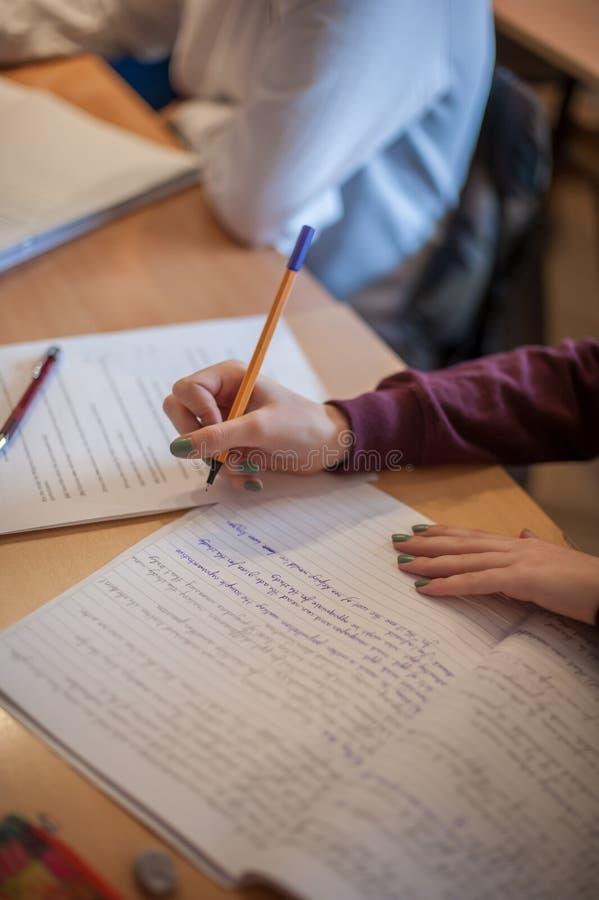 学生手特写镜头在写给笔记本的学校桌上的 免版税库存照片