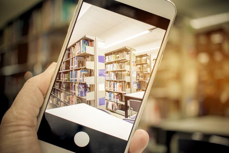学生拿着流动智能手机,在迷离图书馆书柜自然本底,在.图片