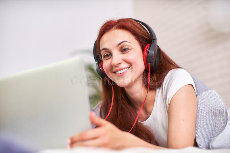学生是愉快与朋友沟通通过互联网 家教,工作和研究,新知识 在床上的愉快的青少年 免版税库存图片