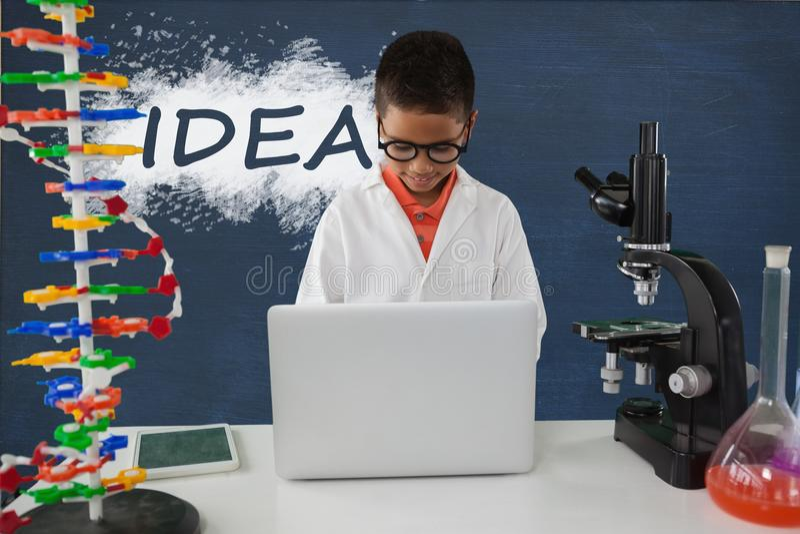 学生男孩在使用一台计算机的桌上反对有想法文本的蓝色黑板 免版税库存照片