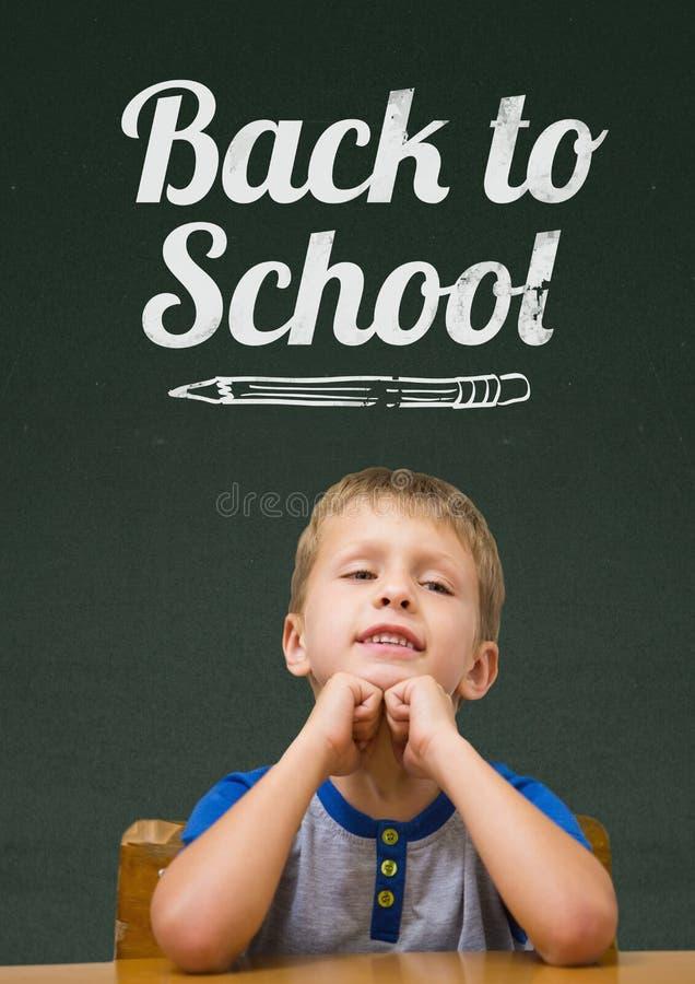 学生男孩在反对绿色黑板的桌上有回到学校课文的 皇族释放例证