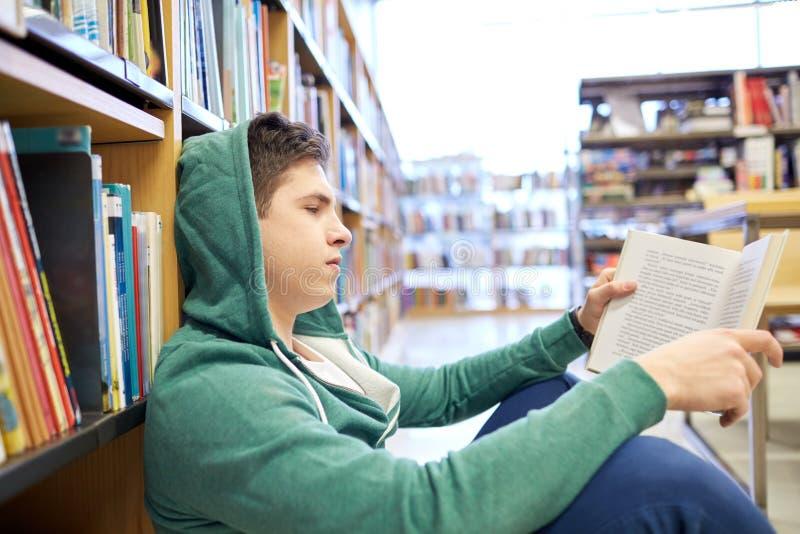 学生男孩或年轻人阅读书在图书馆里 图库摄影