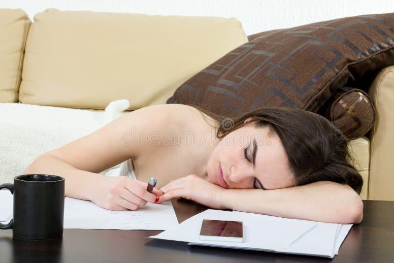 学生疲倦了和睡觉在她的在笔记的客厅 免版税库存照片