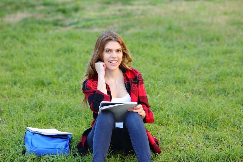 学生看照相机坐草 免版税图库摄影