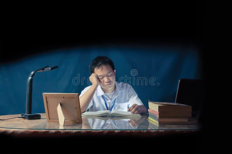 学生睡着,当学习在书桌时 在玻璃后被射击的办公室室 图库摄影