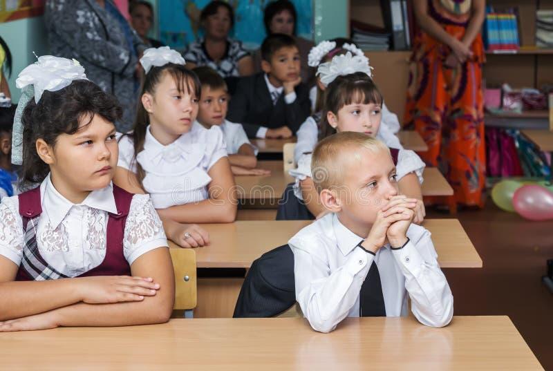 学生第4年级在有他们的父母的9月1日教室 库存图片