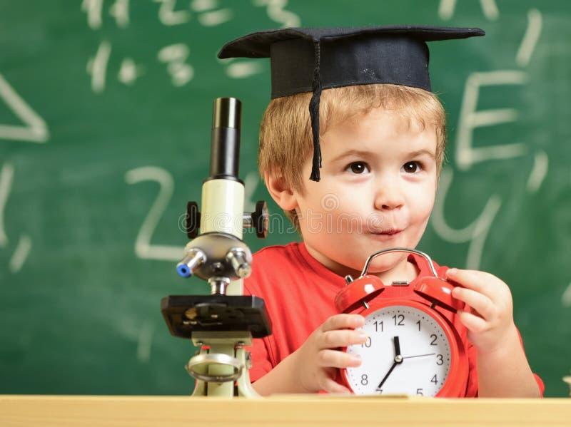 学生等待的学校断裂 激动的面孔的孩子看闹钟 学校断裂概念 院的孩子男孩 库存图片