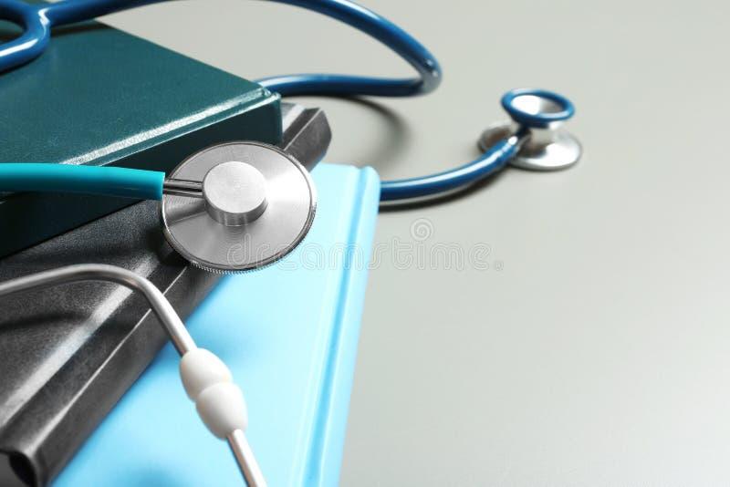 学生课本、听诊器和空间文本的在灰色背景,特写镜头 免版税图库摄影