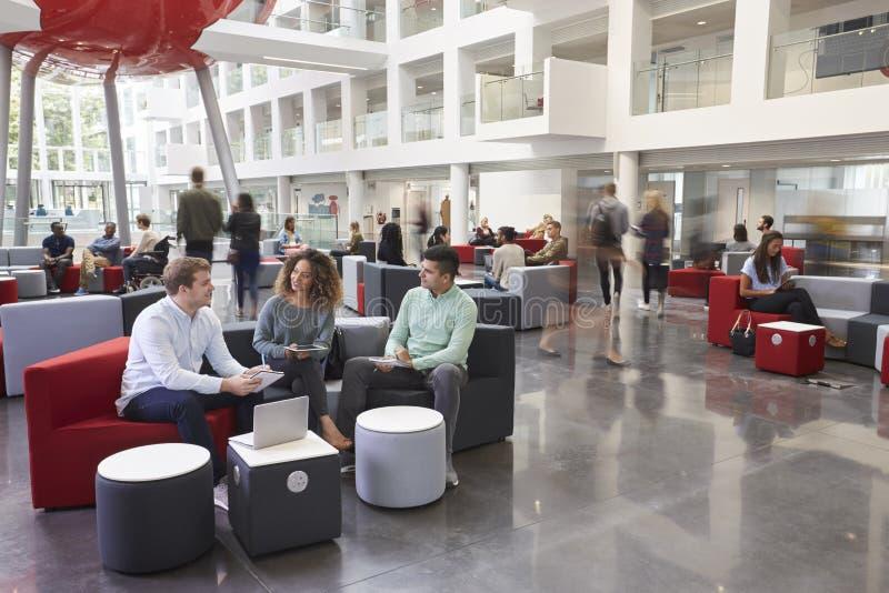 学生谈话在繁忙的大学大厦 免版税图库摄影