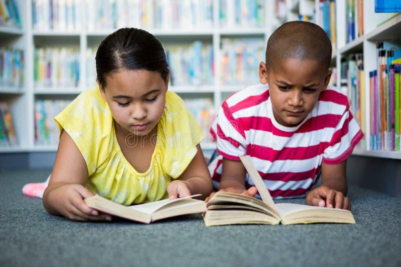 学生阅读书,当说谎在图书馆在学校时 免版税库存照片