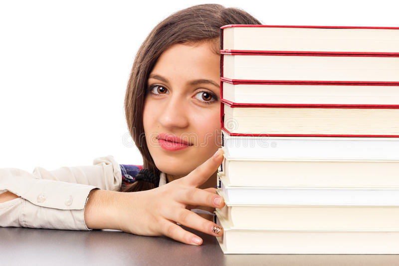 学生面孔特写镜头在堆的书后 免版税库存照片
