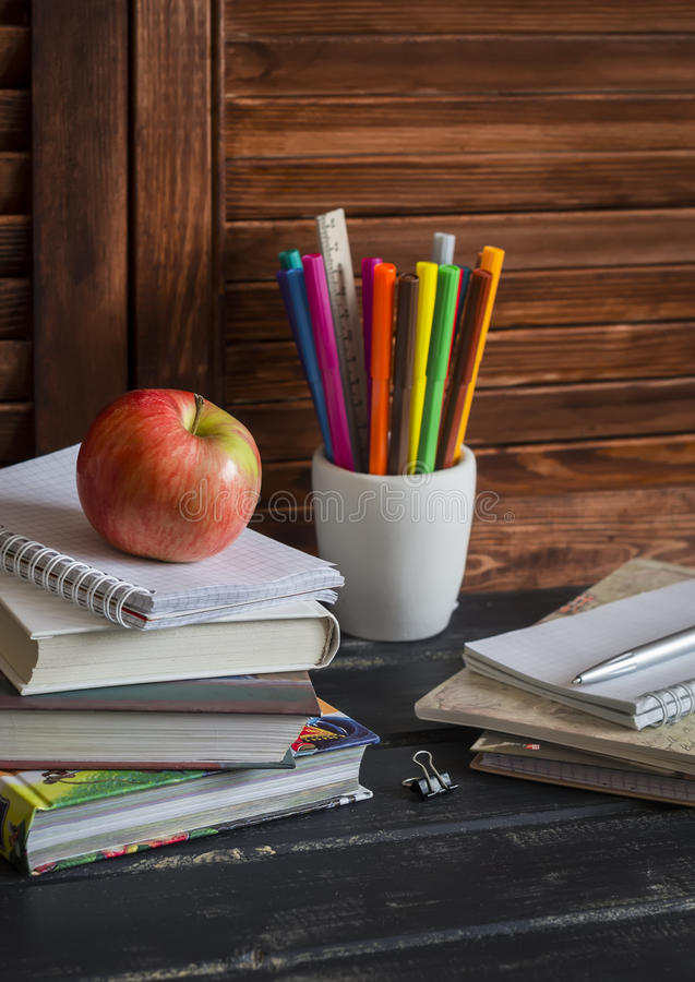 学童和学生研究辅助部件 书,笔记本,笔记薄,上色了铅笔、笔、统治者和一个新鲜的红色苹果 家 免版税库存图片
