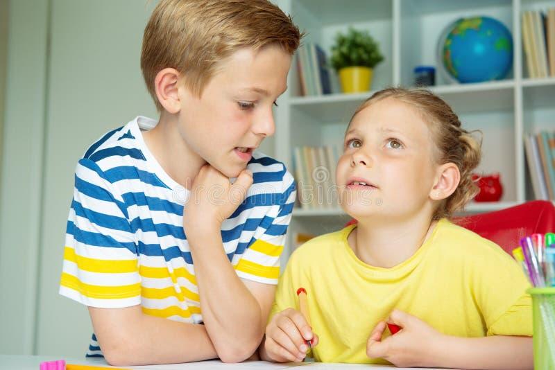 学童是回来了到学校和学会在桌上在教室 免版税库存图片