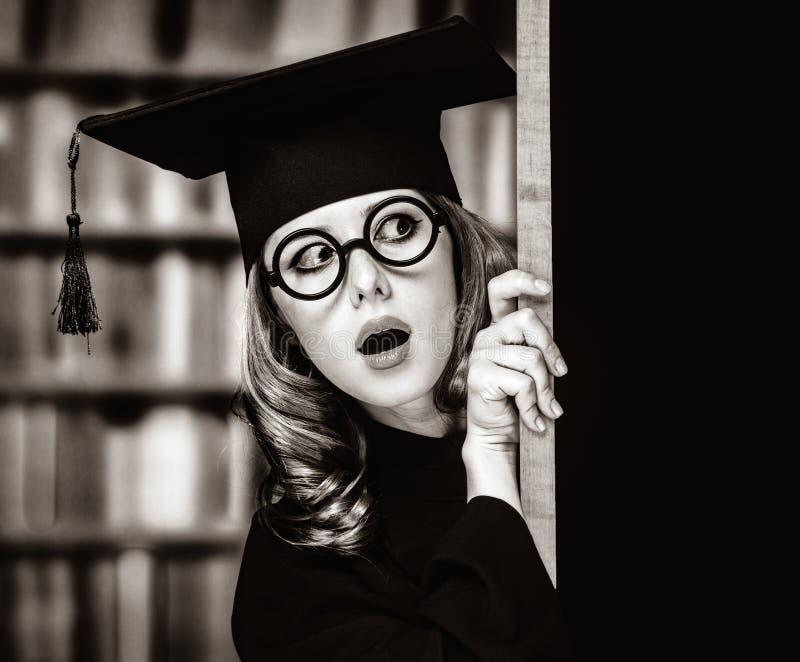 学袍的研究生女孩在黑板附近 图库摄影