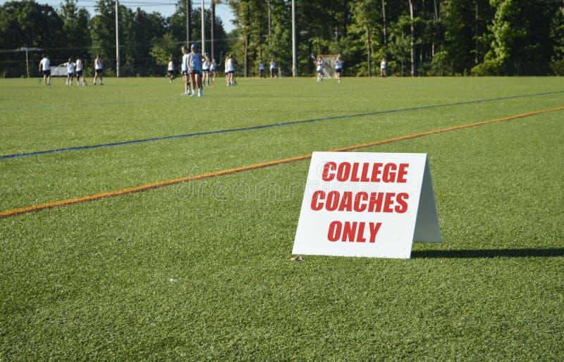 学院教练标志在女孩曲棍网兜球吸收的比赛 免版税库存图片