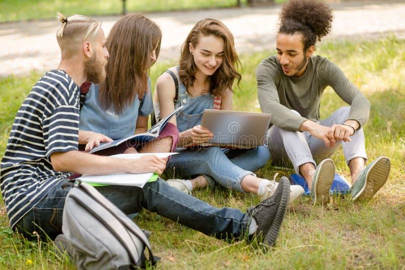 学院朋友坐草坪在校园里,沟通 免版税库存照片