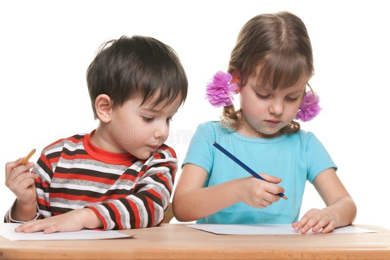 学龄前儿童坐在书桌并且写道 免版税库存图片