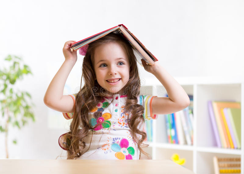 学龄前儿童有书的孩子女孩在她的头 免版税库存照片