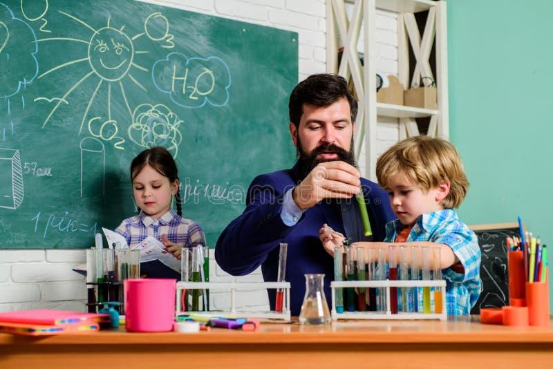 学龄前儿童的俱乐部 化学实验 学校俱乐部交互式教育 老师和学生试管 免版税库存照片