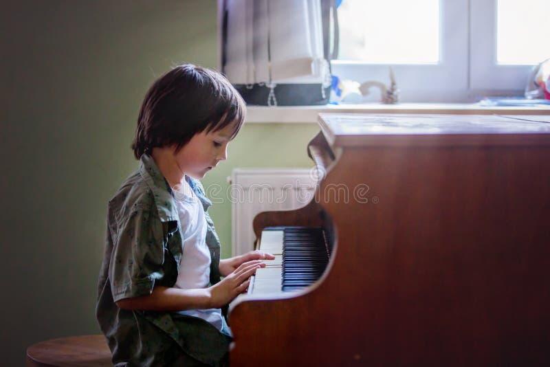 学龄前孩子,逗人喜爱的男孩,在家弹钢琴 免版税图库摄影
