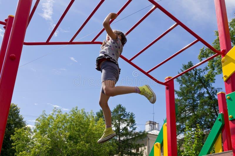 学龄前沿猴子栏杆的女孩垂悬的步行 免版税库存照片