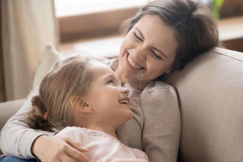 学龄前说谎在长沙发耍笑的笑的女儿和快乐的母亲 免版税库存图片