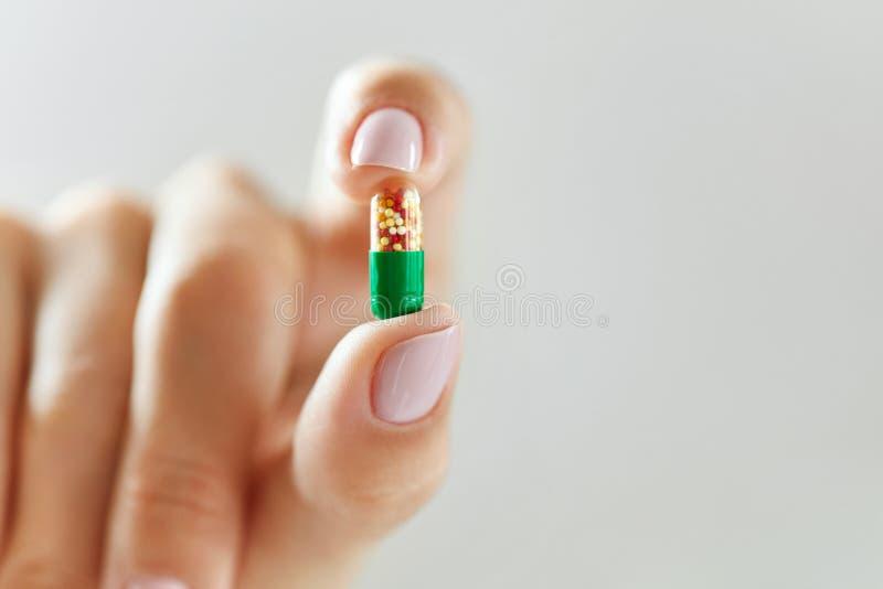 医学 拿着五颜六色的药片,片剂的女性手 免版税库存图片